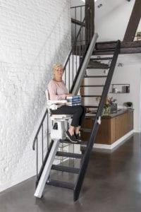 Handicare Trapliften, Vrouw op traplift met boeken - Zandberg B.V.
